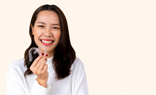beautiful-asian-woman-smiling-with-hand-holding-dental-aligner-retainer-invisible