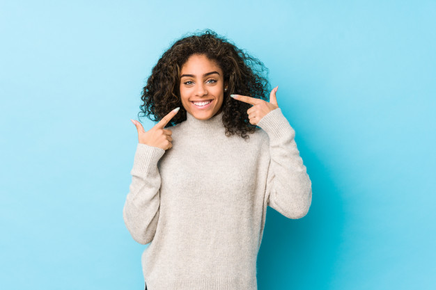 young-african-american-curly-hair-woman-smiles-pointing-fingers-mouth